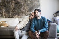 Loving homosexual couple sitting on sofa at home - CAVF44316