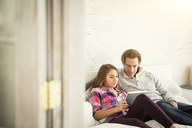 Father and daughter using tablet computer while sitting on bed at home - CAVF44394