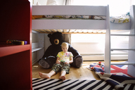 Full length of boy resting on teddy bear under bed at home - CAVF44454