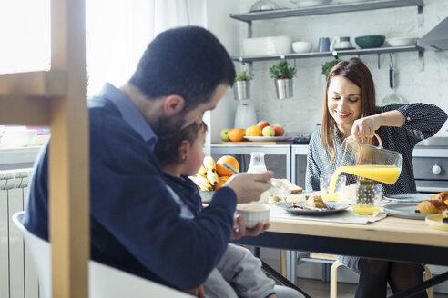 Family having breakfast at table in kitchen - CAVF44466