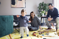 Happy parents looking at son walking in living room - CAVF44481