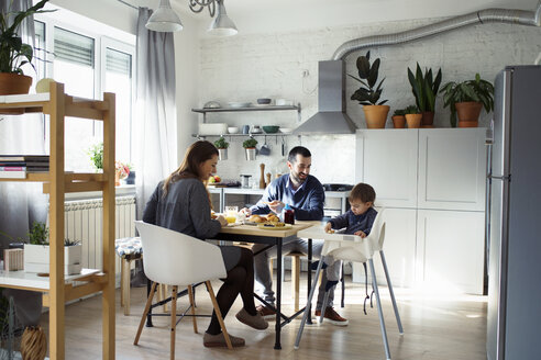 Parents looking at son sitting on high chair while having breakfast in kitchen - CAVF44484