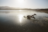 Carefree man jumping into lake against clear sky during sunny day - CAVF44571