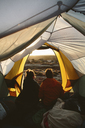 Rear view of friends looking at view while sitting in tent - CAVF44580