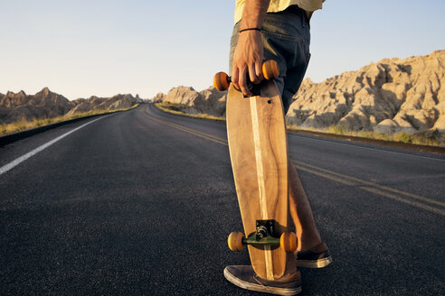 Low section of man holding skateboard while standing on country road on desert - CAVF44583