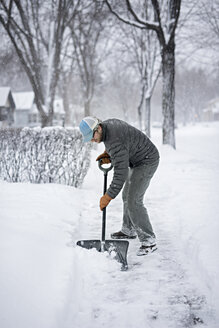 Full length of man shoveling snow from street - CAVF44643