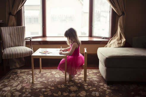 Side view of girl drawing at table in living room - CAVF44652