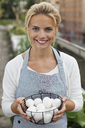 Portrait of happy young woman in apron holding bowl of eggs - MASF06066