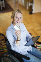 Portrait of happy woman in wheelchair with digital tablet showing credit card - MASF06096