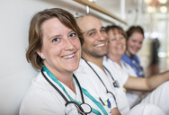 Portrait of happy mature female doctor with colleagues leaning on wall in hospital - MASF06120