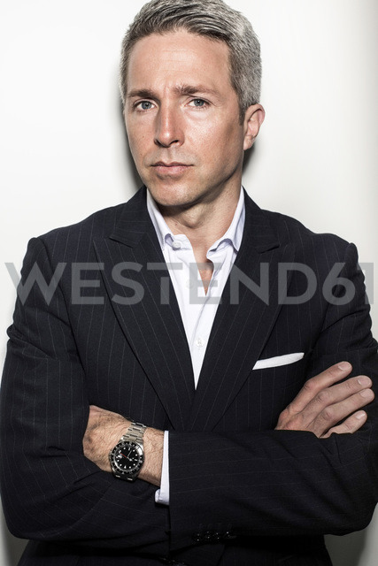 Portrait of mature businessman standing arms crossed against wall - MASF06132
