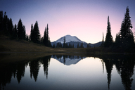 Scenic view of lake and Mount Rainier against sky during sunset - CAVF44784