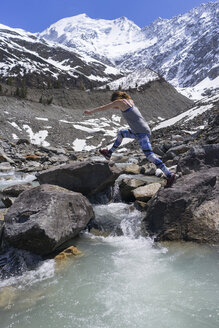 Side view of woman jumping on rocks by river against snowcapped mountains - CAVF44796