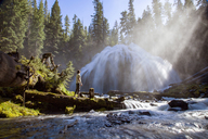 Man standing on field against Chush Falls on sunny day - CAVF44802