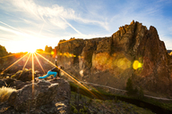 Woman stretching on rock against mountains at Smith Rock State Park on sunny day - CAVF44811