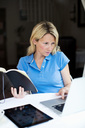 Mid adult woman with book and digital tablet using laptop - MASF06150