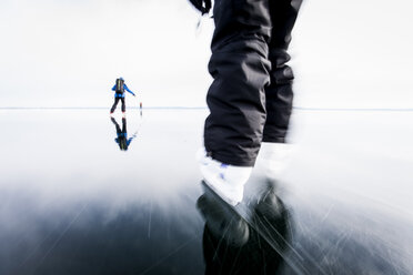 People skiing on frozen lake against clear sky - MASF06183