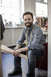 Portrait of confident happy male fashion designer sitting in studio - MASF06189