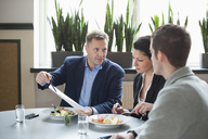Mature businessman with colleagues discussing paperwork at restaurant table - MASF06228