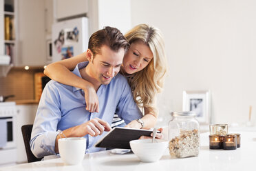 Man using digital tablet with woman arm around him at breakfast table - MASF06240