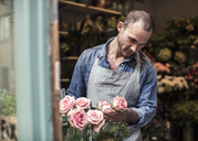 Mid adult male florist analyzing flowers at shop - MASF06249