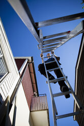 Low angle view of man climbing ladder against clear sky - MASF06264