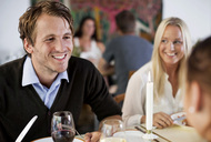 Happy young man with friends at restaurant table - MASF06273