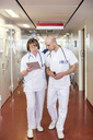 Male and female doctors using digital tablet while walking in hospital corridor - MASF06321