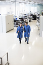 High angle view of male and female engineers discussing while walking in factory - MASF06333
