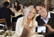 Happy friends posing for photograph in restaurant - MASF06339
