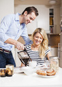Happy man serving black coffee for woman at breakfast table - MASF06387