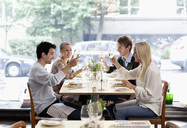 Group of friends toasting wineglasses at restaurant table - MASF06426