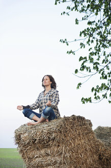 Full length of young woman meditating on haystack - MASF06438
