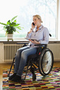 Disabled woman with digital tablet using mobile phone while sitting in wheelchair at home - MASF06441