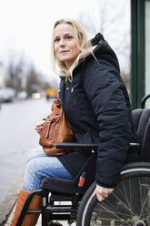Disabled woman in wheelchair looking away outdoors - MASF06444