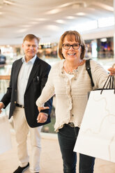 Excited senior woman pulling man in shopping mall - MASF06447