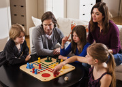 Family playing ludo together at table in living room - MASF06453