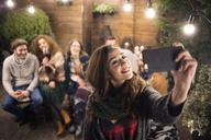 Woman taking selfie with friends in backyard at night - CAVF45214