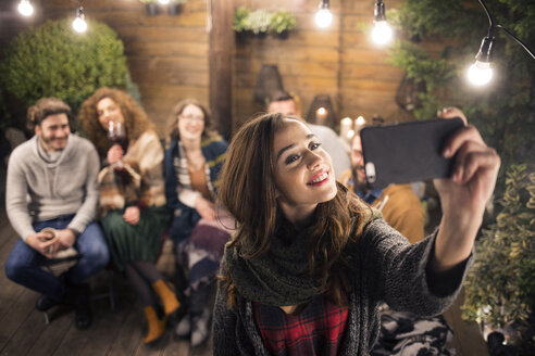 Woman taking selfie with friends in backyard at night - CAVF45214