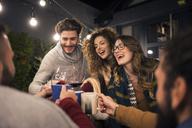 Happy friends toasting drinks in backyard at night - CAVF45223
