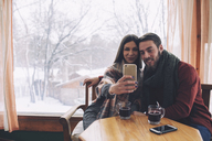 Woman with boyfriend taking selfie while sitting by window in cafe - CAVF45226