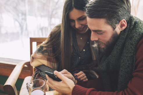 High angle view of couple using mobile phone in cafe - CAVF45229