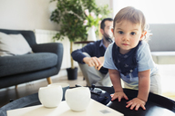 Portrait of baby boy standing by table with father in background at home - CAVF45244