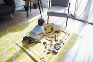 High angle view of baby boy playing with toy train at home - CAVF45247
