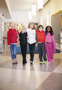 Portrait of friends with arm around walking in school corridor - MASF06524