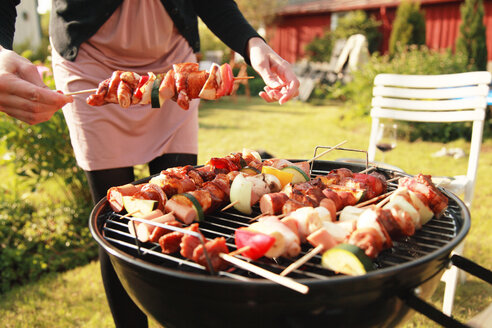 Midsection of holding skewer with barbecue grill - MASF06533