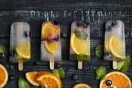 Homemade detox popsicles with blueberries, orange slices and mint leaves on black wood - RTBF01166
