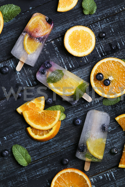 Homemade detox popsicles with blueberries, orange slices and mint leaves on black wood - RTBF01169