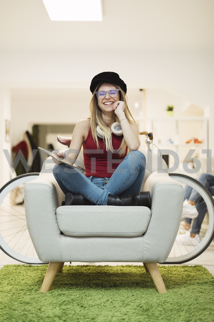 Happy casual young woman with tablet in coworking space - OCAF00213