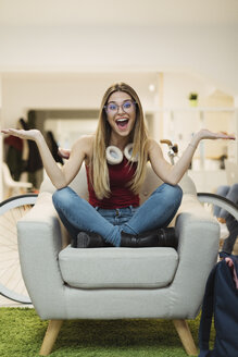 Happy casual young woman sitting in armchair in coworking space - OCAF00219